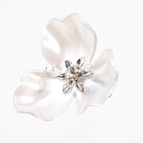白いビンテージパーツの上にデジンで小さい花とクリスタルを止めて作られています