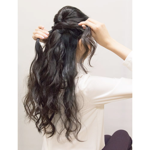 2. 左右の顔周りの髪の毛をねじりながら、後ろへ持っていき、ピンで留める