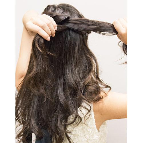 2. 左横の髪の毛を右へとねじり編みをする